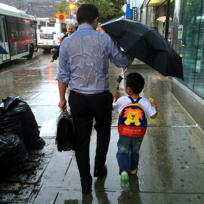 daddy drench rain holding umbrella to son viral photo