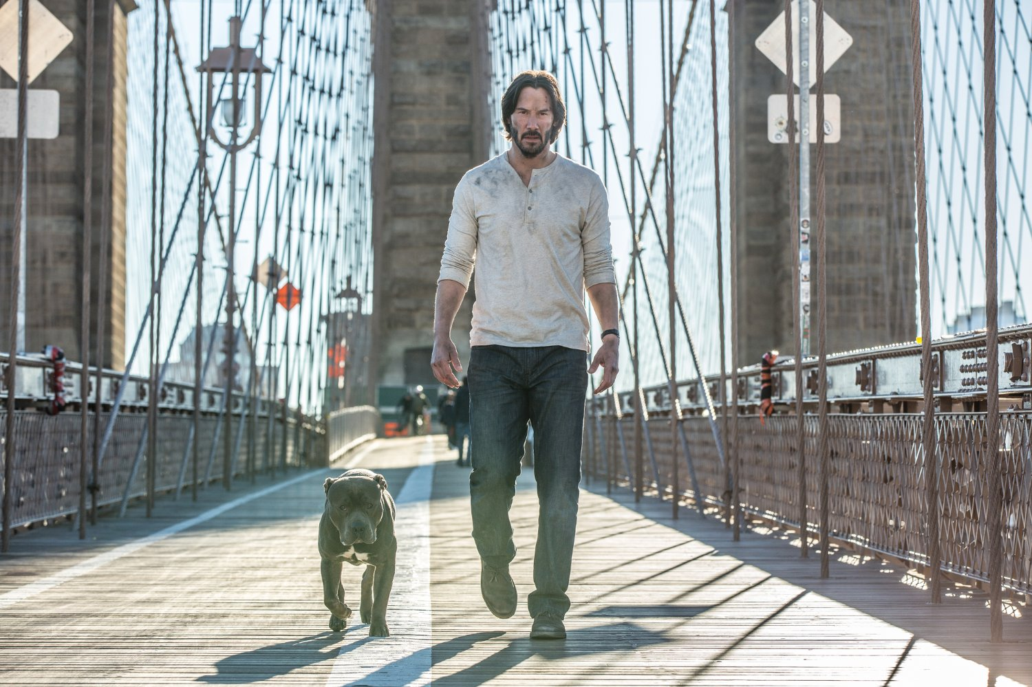 John Wick with pitbull walking Brooklyn bridge